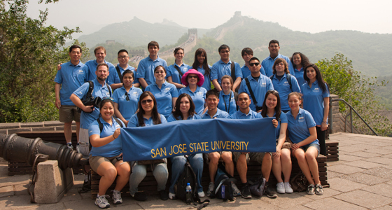 SJSU students and faculty wear matching blue polo shirt and hold a SJSU banner at the Great Wall of China as part of the 2011 Global Technology Initiative trip. Photo by Clifford Wong.