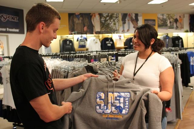 Bookstore workers examine SJSU logo attire.