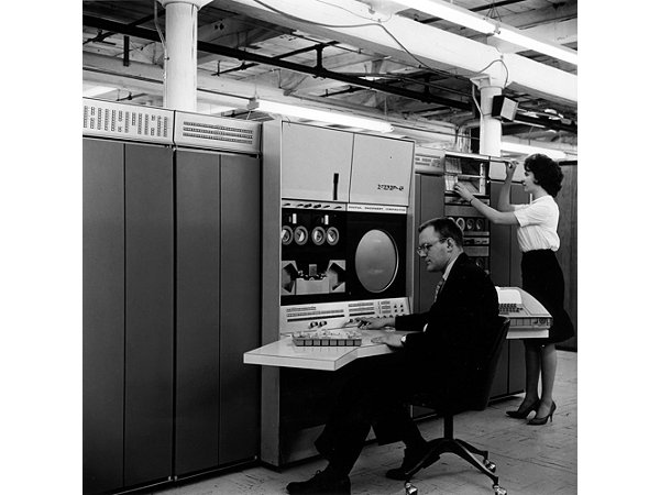 Gordon Bell typing on the keyboard of a computer the size of a refrigerator.