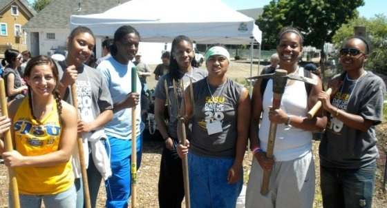 Members of the women's basketball team holding tools outdoors at the 2010 Day of Service