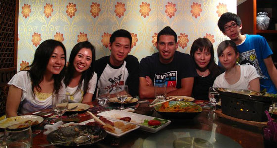 Marco Henry sitting with group in China having dinner.