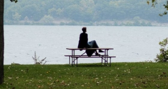 Film subject sitting on bench with scenery including pond in the background.