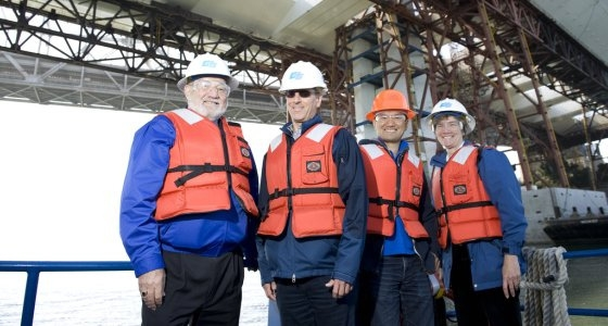 The provost, Steve Holsebus and 2 engineering profs on a boat below the new East Span for the Bay Bridge.