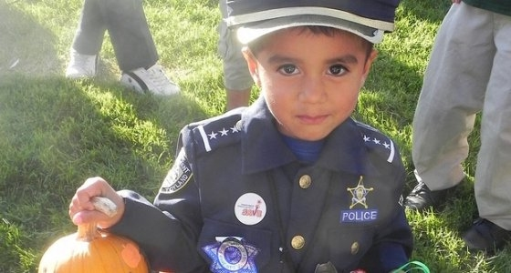Little boy dressed in a police officer costume holding a tiny pumpkin.