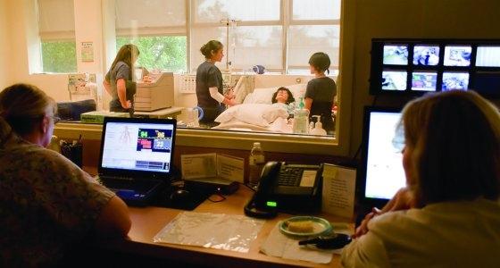 Nursing faculty members observe students working in the nursing sim lab.