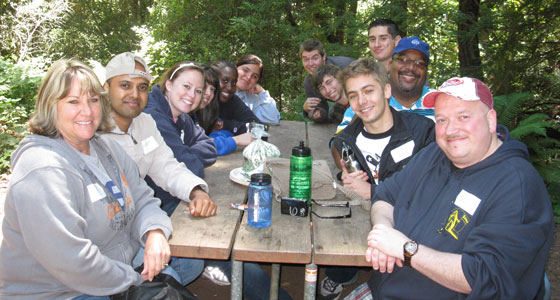 Rich Kelley and Cheryl Vargas sit around a table with SJSU students surrounded by trees at the 2010 A.S. Retreat.