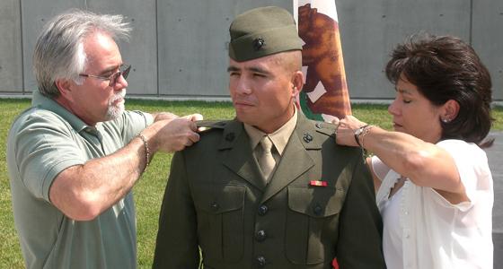 Jack Harding, left, and Natalie Harding pin lieutenant stripes to the uniform of their son, Jack Jr. Photo courtesy of Jack Harding.