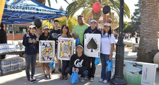 Group of students and employees, some wearing large playing cards, in celebration of the Poker Walk fitness event.