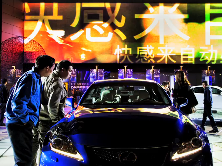 Image from essay showing everyday people examining a fancy sports car.