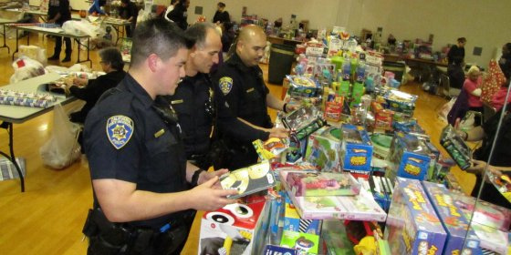 3 UPD officers in uniform sort a huge pile of toys ready to be wrapped.
