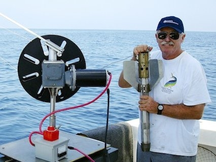 "scientist at sea with a ""corer"" used to drill down into the ocean floor"