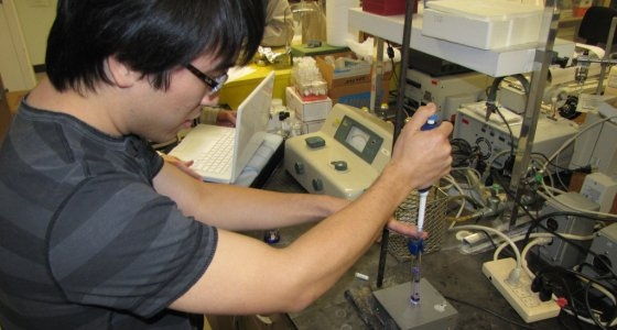 male researcher holding a syringe-like instruments over a plate in a lab full of equipment