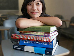 teaching student resting in pile of books