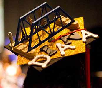 "Close up of 3D bridge and small monuments with the name ""Diana"" on a woman's graduation cap. Photo by Christina Olivas."