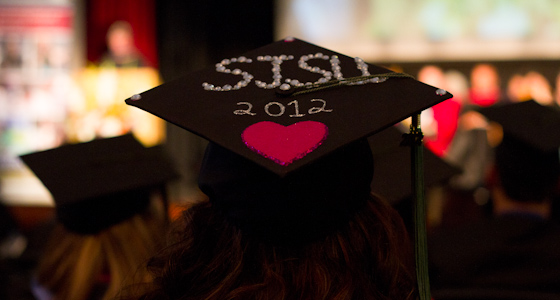 "A close-up of a black graduation cap with the words ""SJSU 2012"" and a magenta heart. (Dillon Adams photo)."