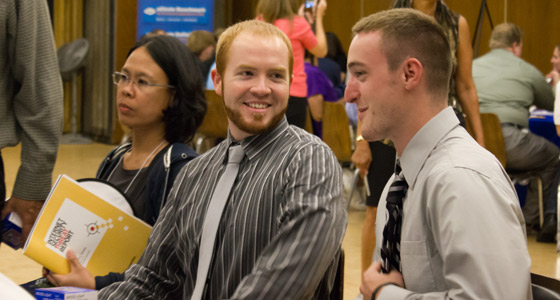 Two young men wearing ties and collared shirtschat during the Cyber Challenge job fair.