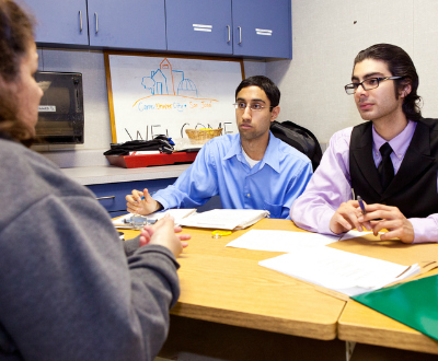 Students meeting with a client.