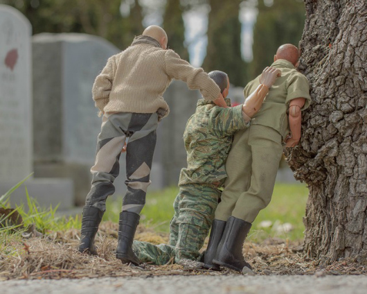 Soldiers, represented by action figures, mourn the loss of a comrade, with gravestones in the background.