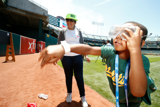 Gurdeep Soi, '15 Electrical Engineering, helps a Richmond Little League baseball player with a hands-on exercise illuminating the science of sports (image courtesy of Chevron).