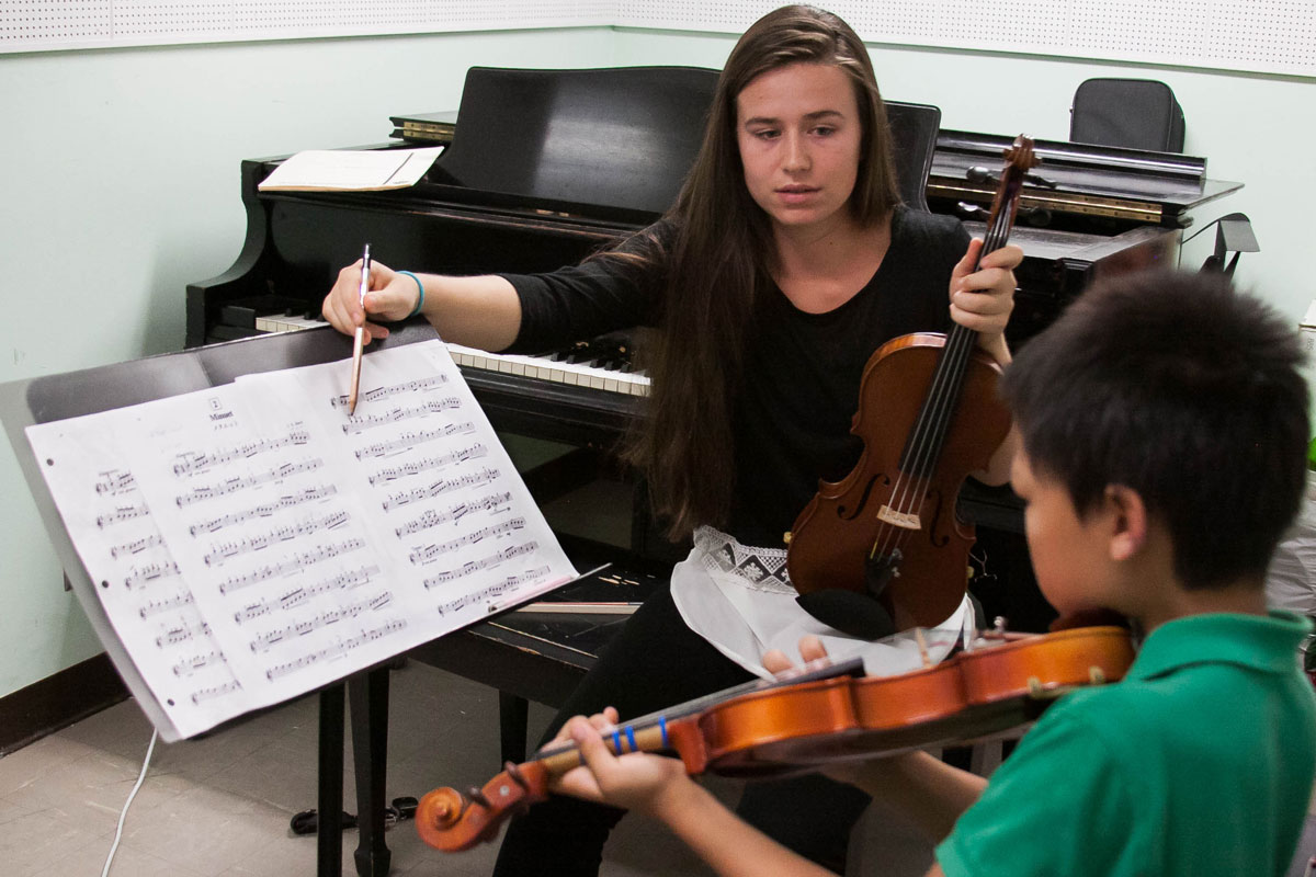 SJSU student gives a one-on-one violin lesson to a boy.
