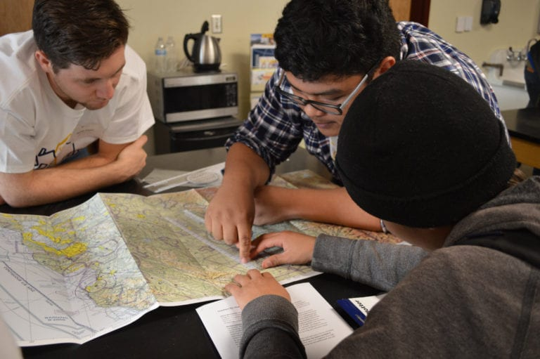 SJSU Aviation majors teach a prepared lesson on aviation navigation to a student in San José High School's robotics club.