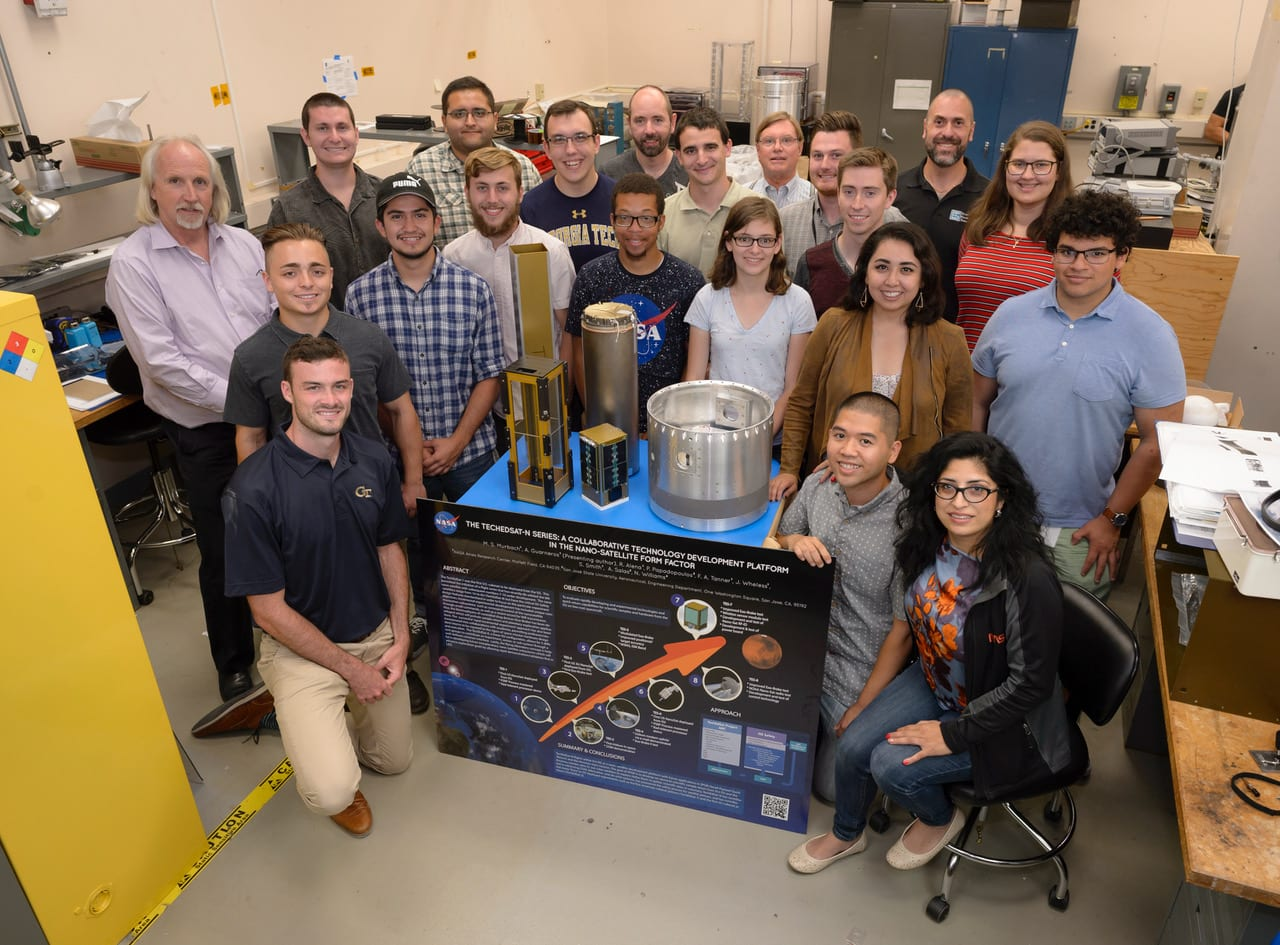 TechEdSat group in N-244 Lab 9 with mentors Mark Murbach (standing back left) and Ali Guarneros Luna (kneeling on right). Photo courtesy of NASA Ames Research Center.