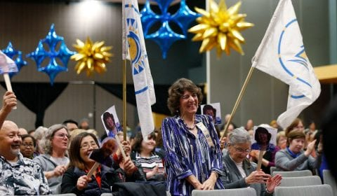 Sharon Brook, an accompanist, is cheered for 40 years of service by colleagues with Spartan banners. ( Josie Lepe/San Jose State University )