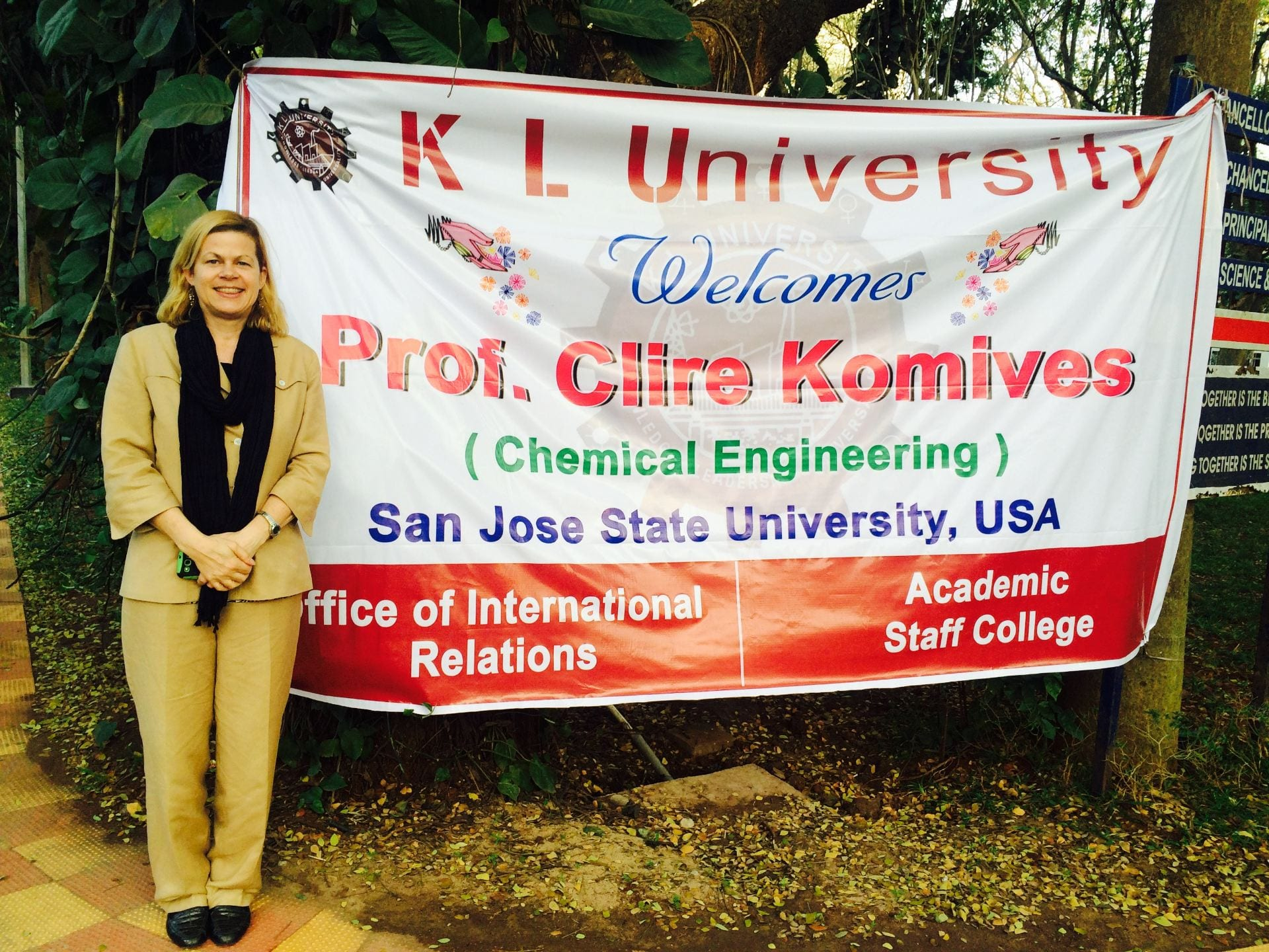 Professor Claire Komives stands in front of a welcome banner at a university in India. She will again travel to the country as a Fulbright Scholar in fall 2019, when she will visit as many as 75 colleges and universities in hopes of enhancing engineering education.