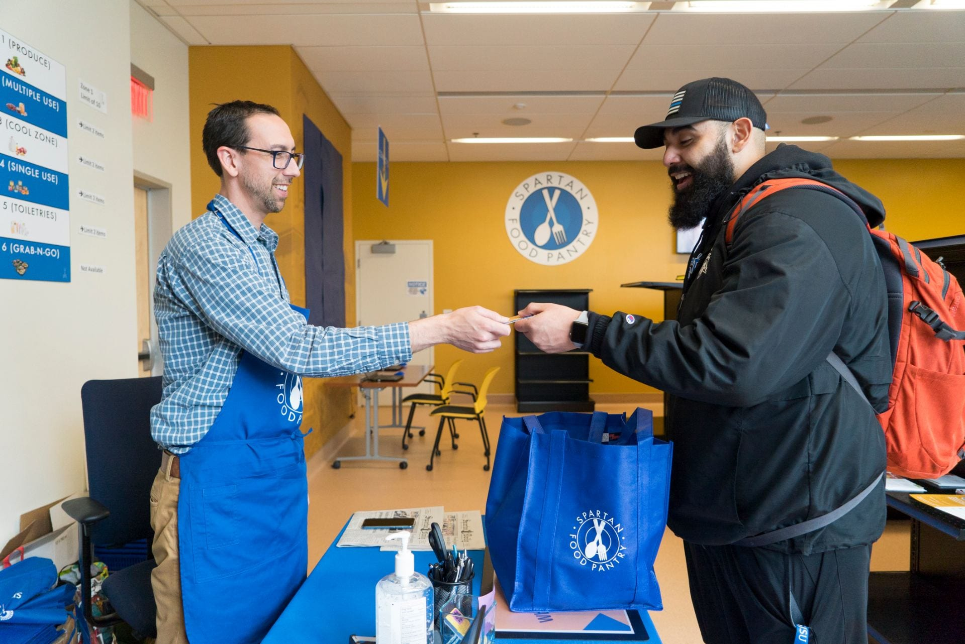 Ben Falter, left, a senior student affairs case manager, helps a student at the Spartan Food Pantry. Photo by Brandon Chew