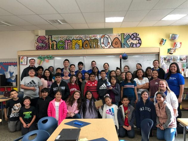 SJSU students pose for a photo with elementary school children who participated in the month-long Cyber Spartan after school program.