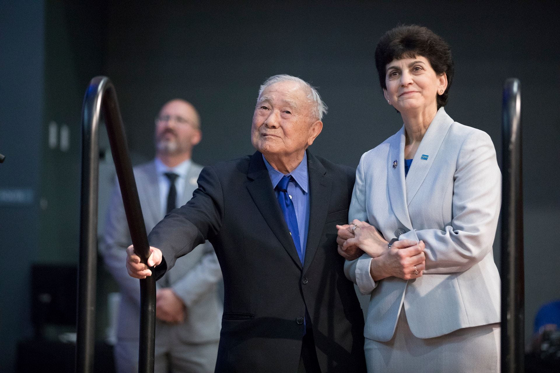 Yoshihiro Uchida, '47 Biological Sciences, walks to the stage with President Mary Papazian during the 2018 Faculty Service and Recognition Awards when he was honored for 70 years of service to SJSU. Photo by David Schmitz