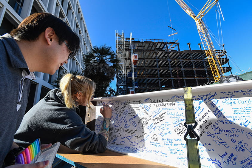SJSU students sign their names for the topping out event.