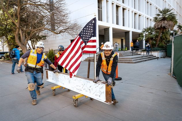 Two construction workers moving the signed ISB beam.