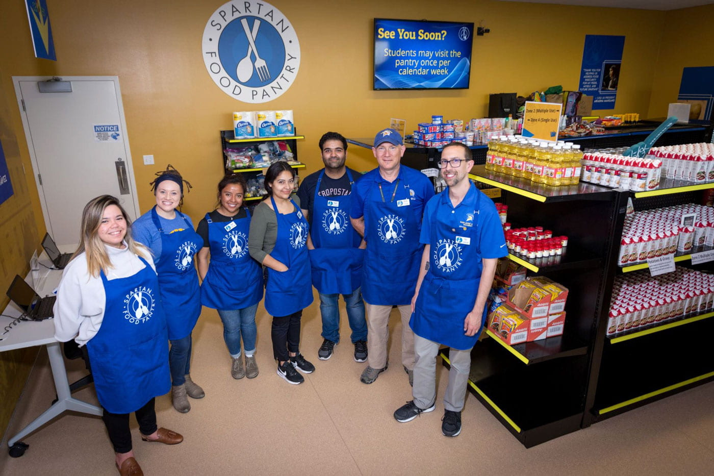 Food Pantry employees in blue aprons.