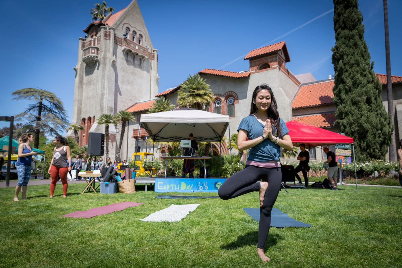 Student on the tower lawn doing a yoga pose.