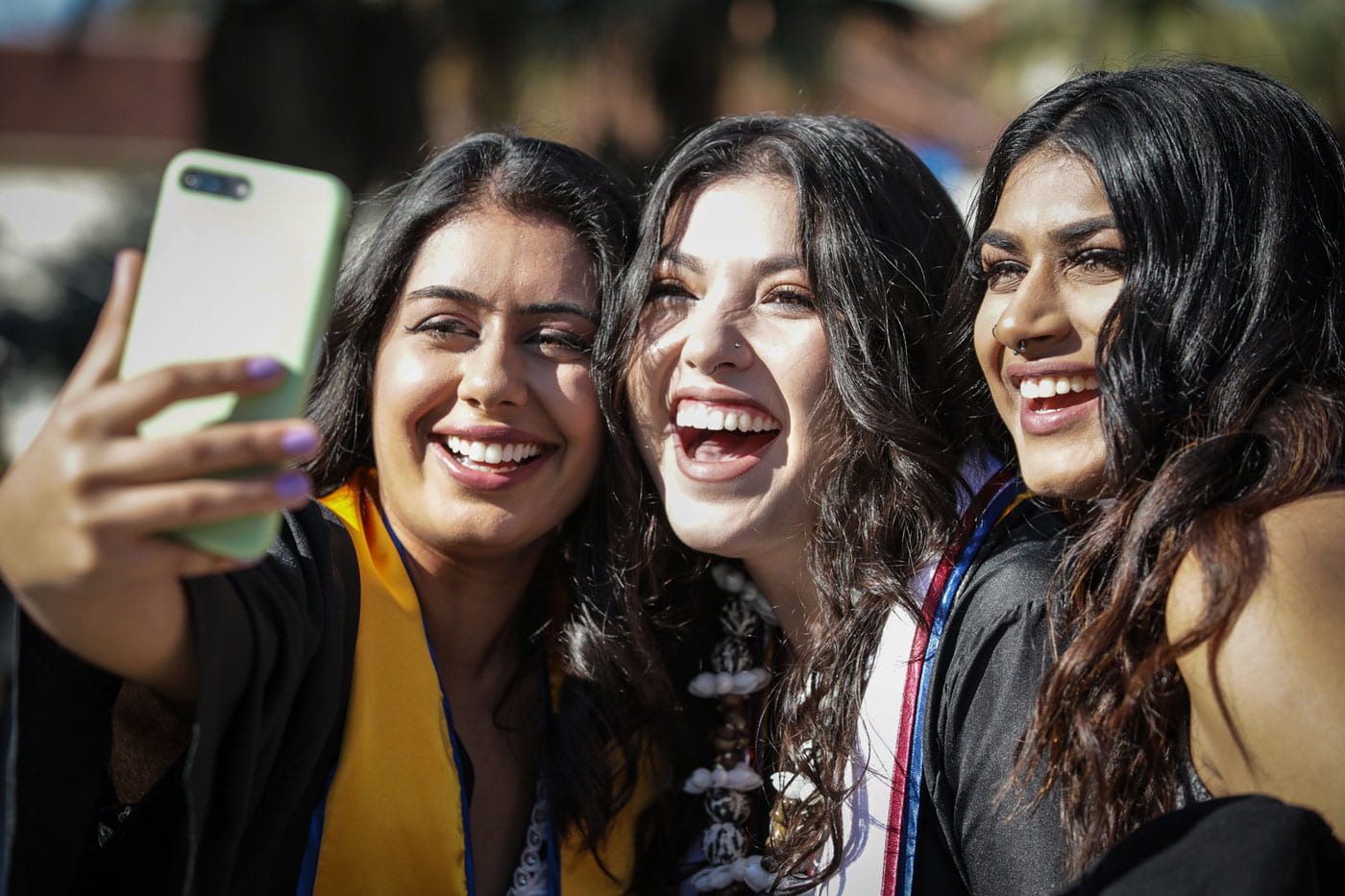 SJSU graduates smile while taking a selfie.