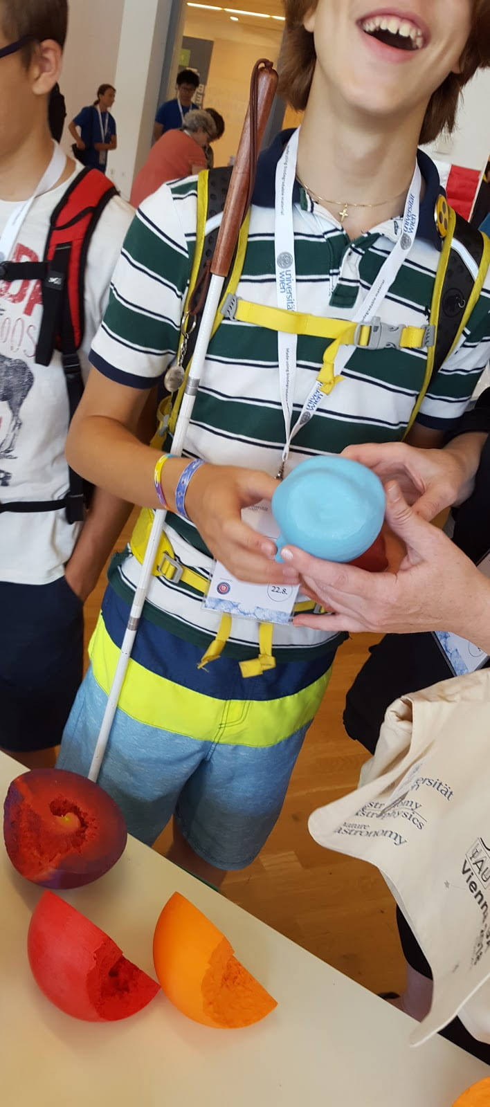 A student with visual impairment holds a 3D printed model of the Eta Carinae Homunculus nebula.