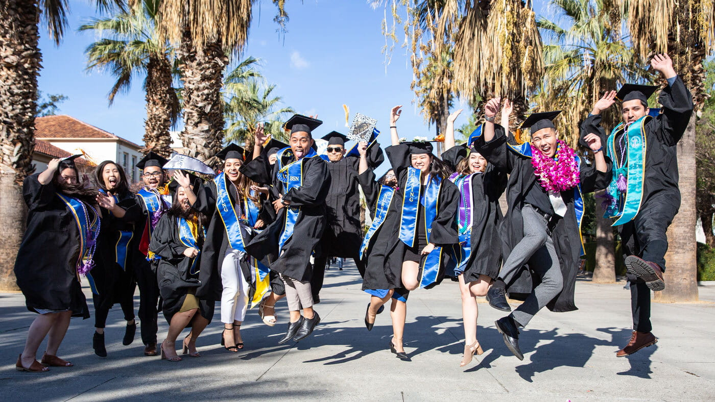 SJSU graduates jumping in the air to celebrate their graduation