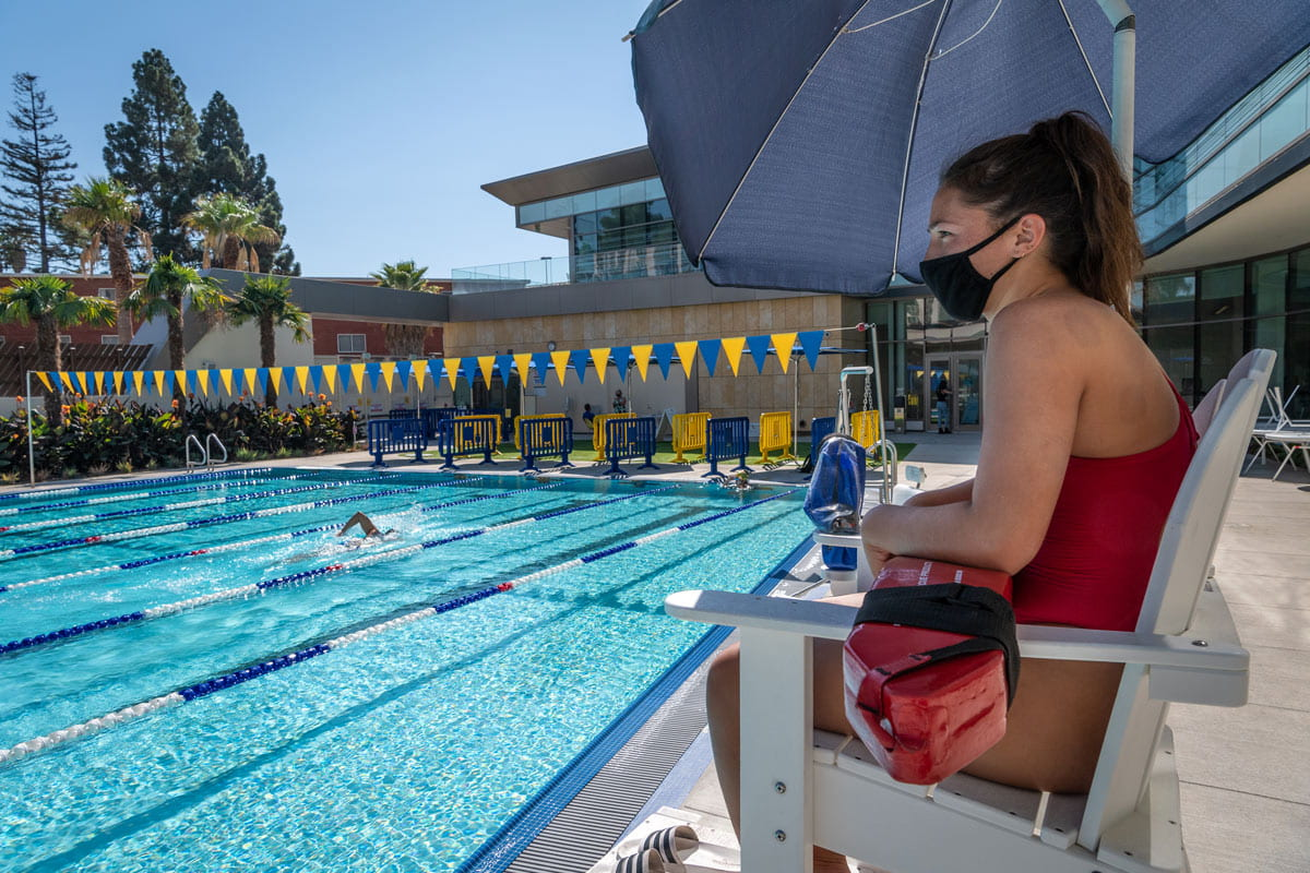 A lifegaurd wearing a mask watches a swimmer doing laps in the SRAC.