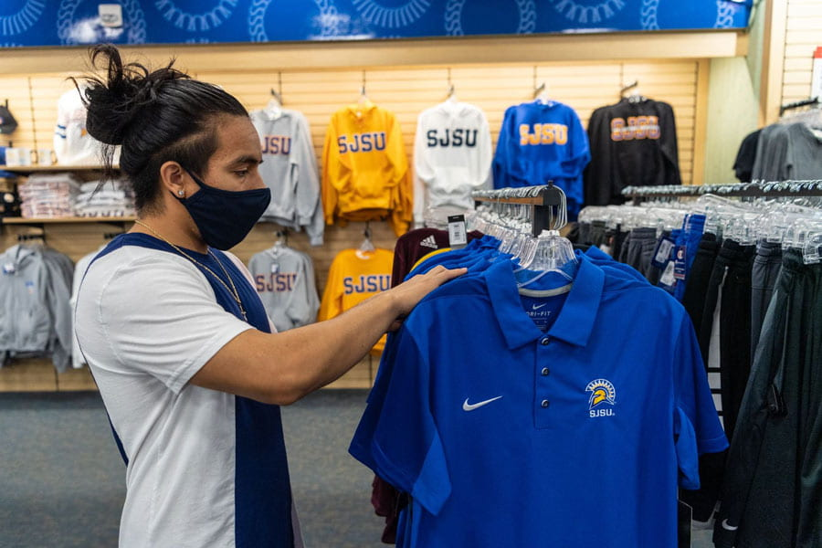 Student wearing a mask in the Spartan Bookstore looking through apparel.