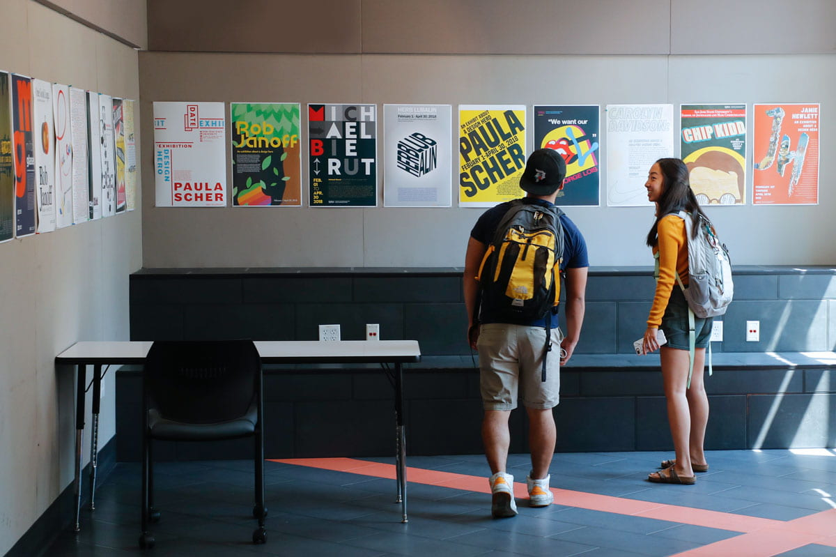 A female and make student smile while admiring graphic design posters lined up on the wall.