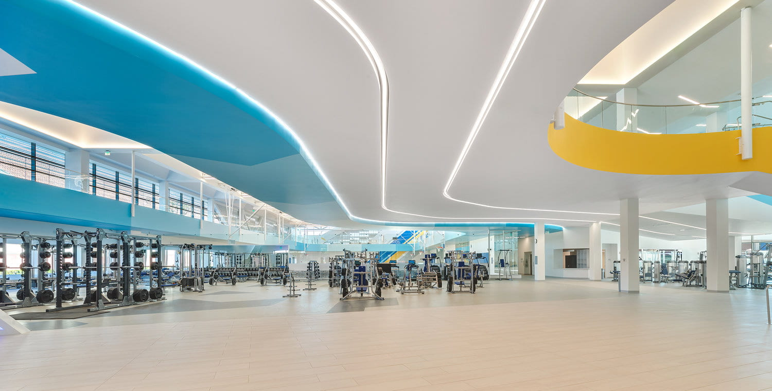 The interior of the SRAC with curving blue, grey and gold ceiling with workout equipment on the floor.