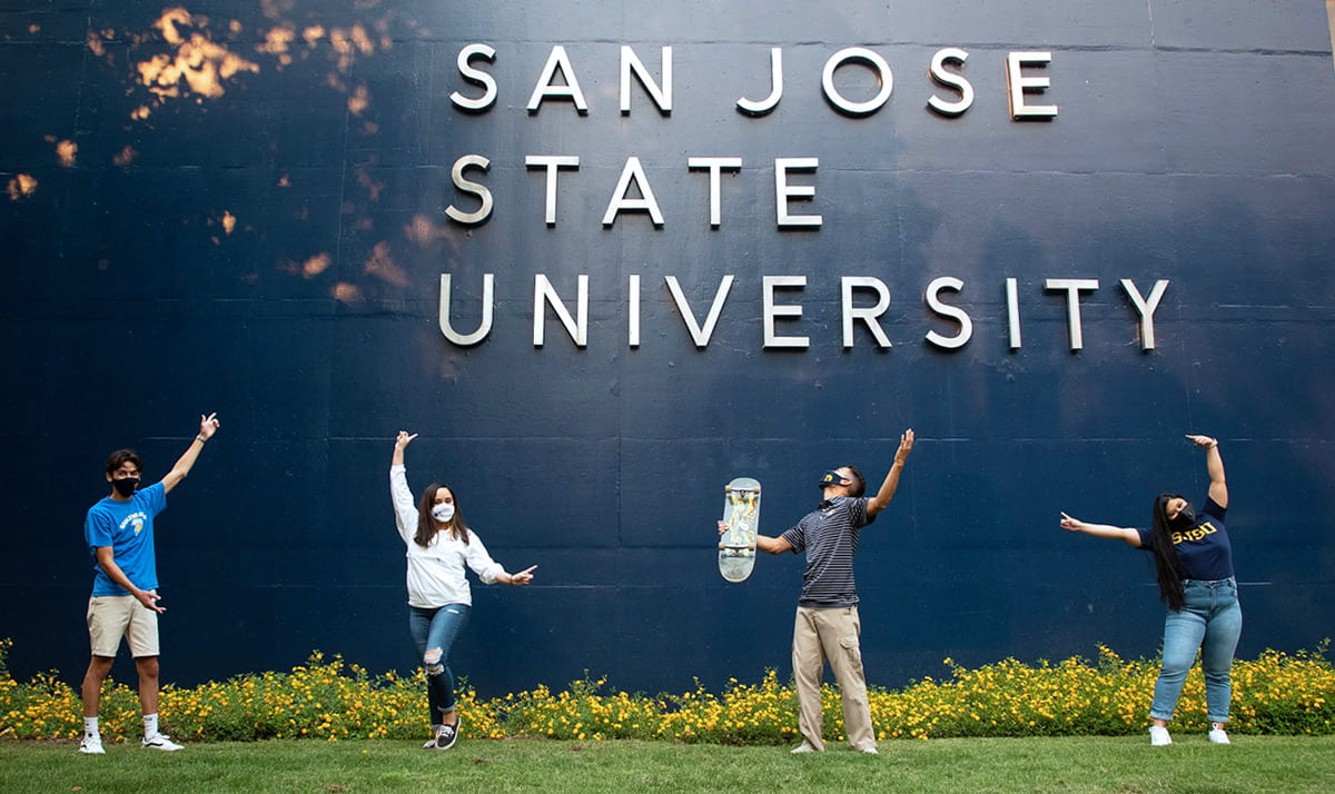 Students pointing to the SJSU sign on a building while wearing masks.