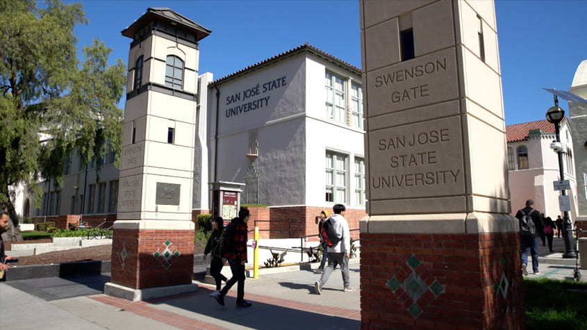 Students walking through the SJSU gates on campus.