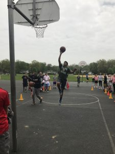 Student jumping to make a basket during SOMS Knockout Challenge