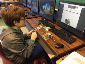 Student building LEGO robot components, looking at computer screen