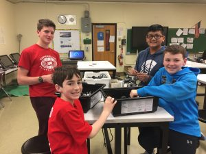 Members of the robotics team smiling in the Challenge Lab