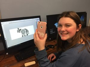 SOMS student Catherine M. with cellphone case design she customized and engraved with new CNC laser cutter
