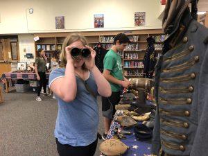 Student looking through Civil War-era binoculars, smiling