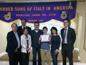 Male student holding certificate surrounded by adults